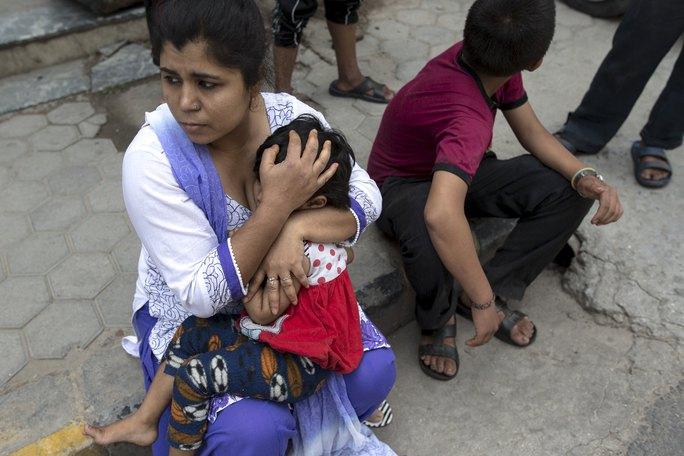 Người mẹ ôm con chạy ra đường khi động đất nổ ra ở Nepal hôm 12-5. Ảnh: Reuters