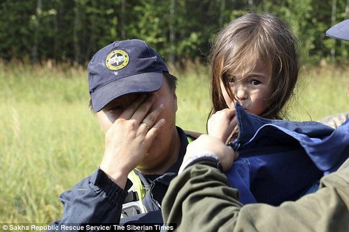 ...cô bé tỏ ra không quá sợ hãi trong khi một nhân viên cứu hộ rơi nước mắt vì tìm thấy em. Ảnh: Siberian Times