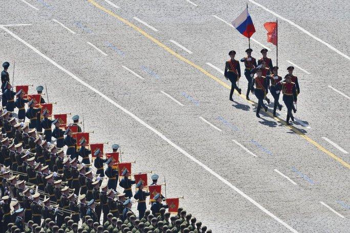Quốc kỳ Nga và lá cờ chiến thắng được rước qua quảng trường. Ảnh: Reuters