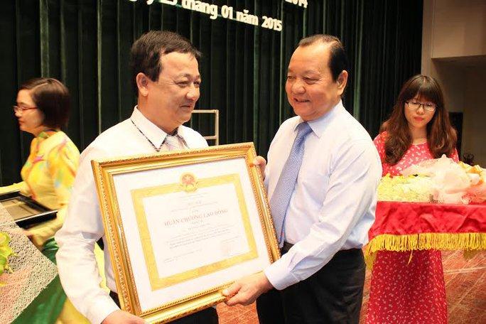 Ông Lê Thanh Hải, Ủy viên Bộ Chính trị, Bí thư Thành ủy TP HCM, trao Huân chương lao động hạng 3 cho ông Trần Đức Phương, Hiệu trưởng Trường Trung cấp Công đoàn TP  Ảnh: HOÀNG TRIỀU