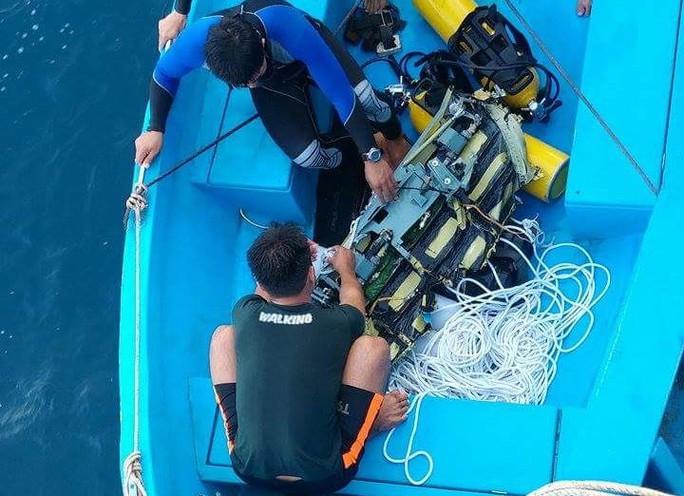 Người nhái chuẩn bị dụng cụ lặn xuống biển vớt thi thể phi công