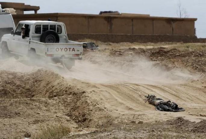 Xe của lực lượng người Shiitte kéo lê thi thể một chiến binh IS trên đường phố. Ảnh: Reuters