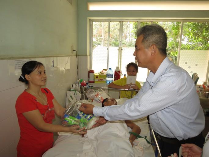 Nam bệnh nhân này không thể tự ngồi dậy, người nhà vui vẻ đón phần quà thay anh.