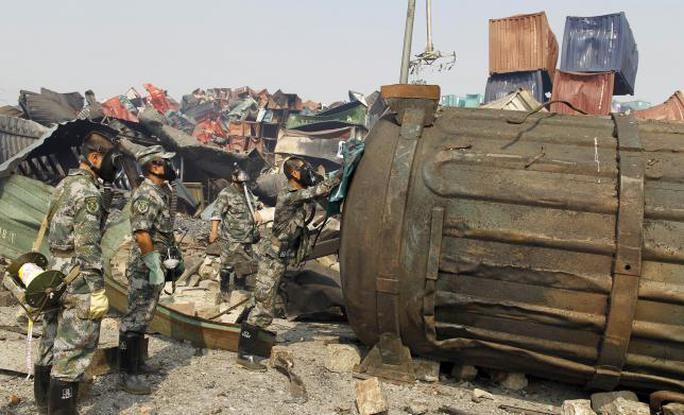 Các binh lính Trung Quốc khẩn trương dọn chất độc. Ảnh: Reuters