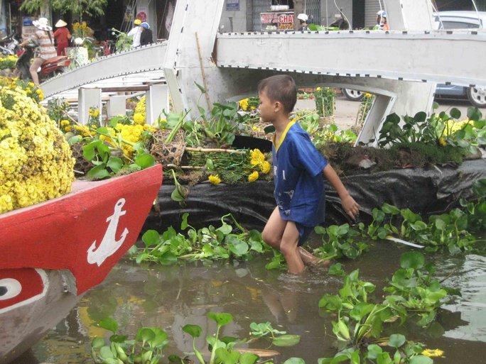 Đứa bé này lội xuống dòng nước phía dưới mô hình cầu Cần Thơ để tìm những gì còn sót lại