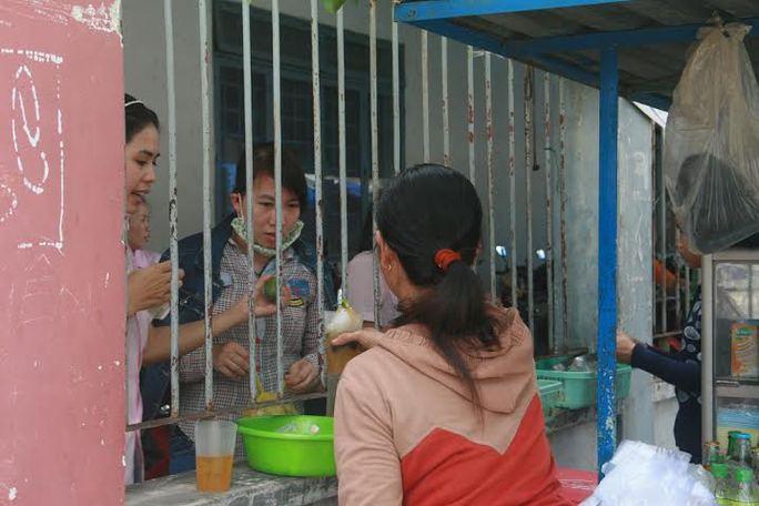 Công nhân của một công ty may tại Cụm CN Trường Xuân (TP Tam Kỳ) không được phép ra bên ngoài nên phải đứng bên trong hàng rào để mua thức ăn  ẢNH: TRẦN THƯỜNG
