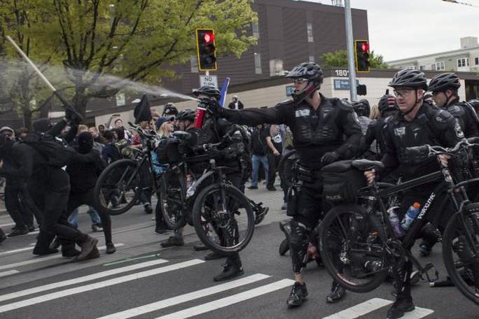 Cảnh sát TP Seattle xịt hơi cay vào người biểu tình hôm 1-5 Ảnh: Reuters