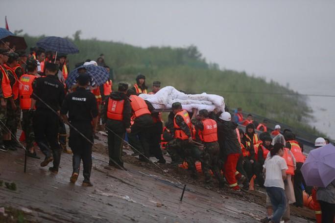 Thi thể một hành khách được đưa lên bờ. Ảnh: China News