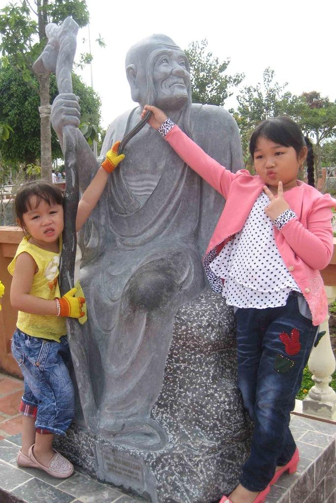 Trẻ em thích thú với những bức tượng đặt trước sân chùa