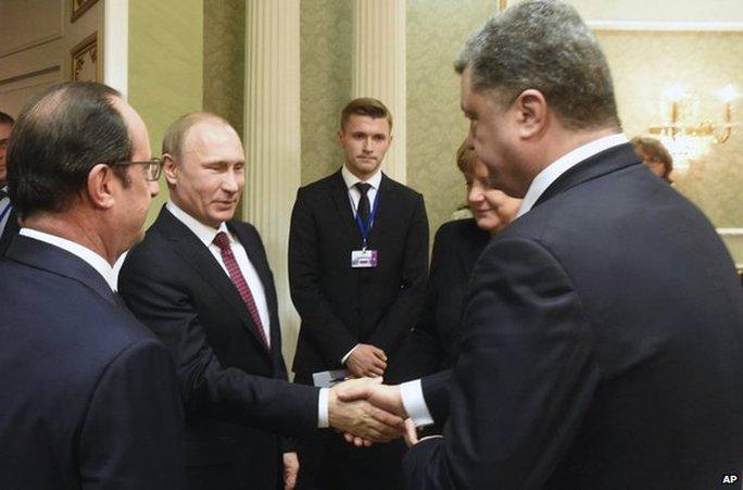 Tổng thống Nga Putin mỉm cười khi bắt tay nhưng Tổng thống Ukraine Poroshenko lạnh lùng. Ảnh: AP