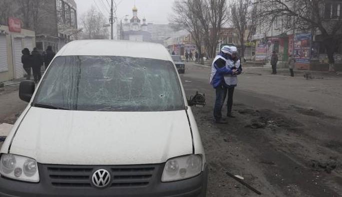 Các chuyên gia của Tổ chức An Nninh và Hợp tác châu Âu (OSCE) đang xem xét các mảnh đạn pháo sau vụ tấn công ở Mariupol, miền Đông Ukraine hôm 24-1-2015. Ảnh: Reuters