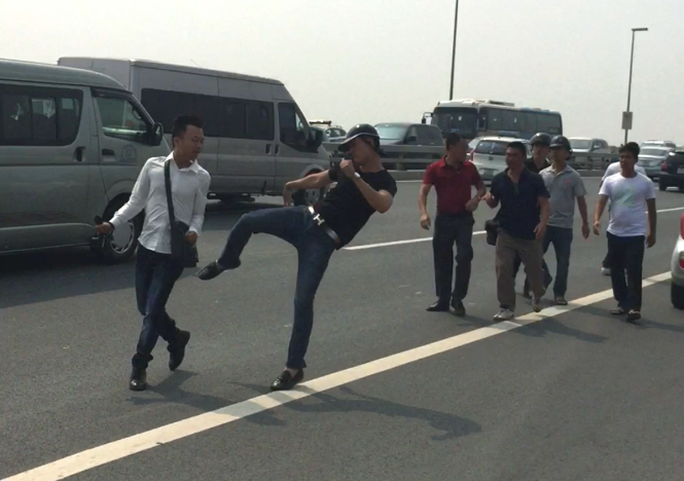 Phóng viên (áo trắng) bị hành hung khi đang tác nghiệp trên cầu Nhật Tân-ảnh: M. C.