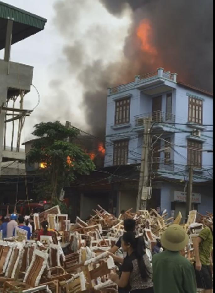 Nhiều người dân giúp chủ xưởng bị cháy chuyển bàn ghế chất đầy đường - ảnh: cắt từ clip