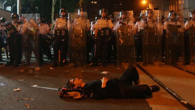 Một người biểu tình nằm ăn vạ trước hàng rào cảnh sát. Ảnh: SCMP