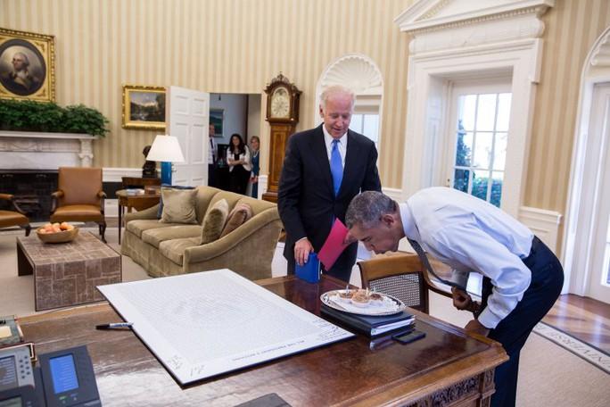 Tổng thống Obama thổi nến trên bánh sinh nhật do ông Biden mang tới Phòng Bầu dục ngày 4-8-2016. Ảnh: NHÀ TRẮNG