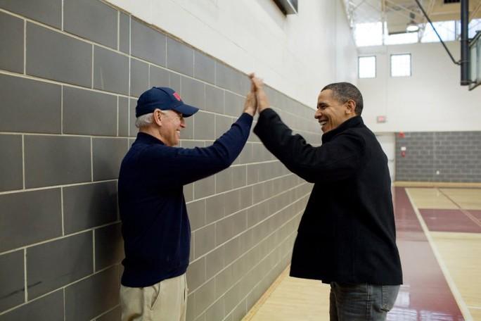 Ông Obama vui vẻ đập tay với ông Biden khi xem hai ái nữ của 2 người Sasha Obama và Biden Maisy chơi bóng rổ ở bang Maryland ngày 27-2-2-10. Ảnh: NHÀ TRẮNG