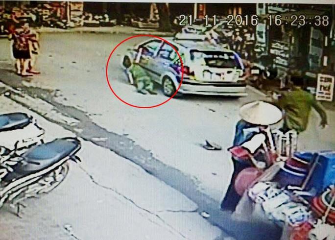 Chiếc taxi kéo lê chiến sĩ công an phường dưới đường - Ảnh cắt từ clip