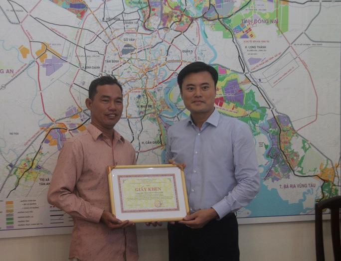 Ông Nguyễn Văn Linh (bìa trái) được Giám đốc Sở GTVT Bùi Xuân Cường trao bằng khen sáng 25-11
