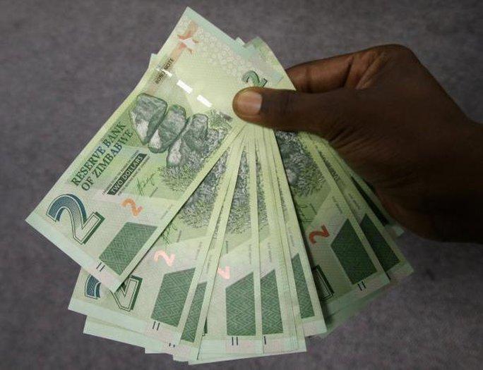 Một người đàn ông Zimbabwe với số tiền trái phiếu rút được hôm 28-11ở thủ đô Harare. Ảnh: REUTERS