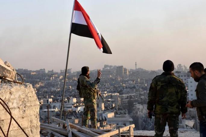Quân đội Syria cắm cờ tại khu phố al-Sakhour, Aleppo vừa được giải phóng. Ảnh: SANA