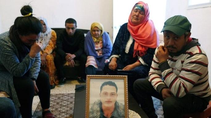 Gia đình Anis bên ngồi quanh bức chân dung của hắn tại Tunisia. Ảnh: EPA