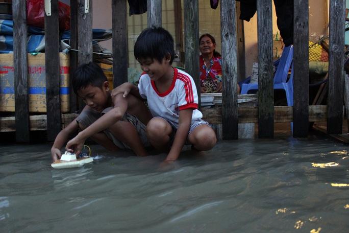 Hai đứa trẻ chơi đùa vui vẻ giữa dòng nước ngập.
