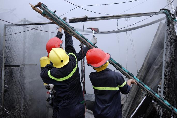 Các chiến sĩ cứu hỏa phải tháo dỡ những bức tường rào bằng thép để có thể tiếp cận bên trong hiện trường vụ cháy.