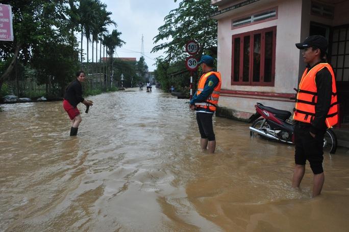 Vì nước lũ ngập sâu nên nhiều nơi phải bố trí lực lượng thanh niên xung phong canh chừng, đề phòng hiểm nguy. Ảnh: Tử Trực