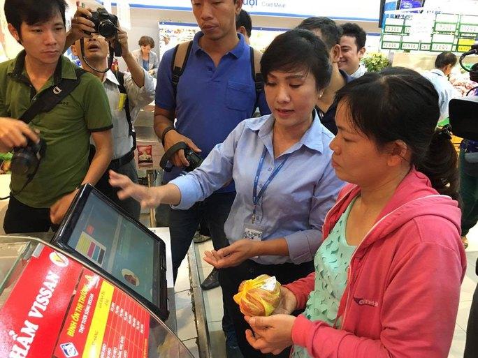 """Nhân viên Co.opmart Foodcosa hướng dẫn khách hàng cách """"soi"""" tem nhận diện nguồn gốc thịt heo"""