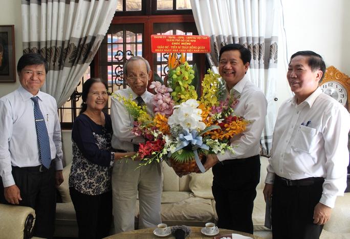 Bí thư Thành ủy TP HCM Đinh La Thăng tặng hoa chúc mừng GS-TS Trần Hồng Quân - Ảnh: Bảo Ngọc