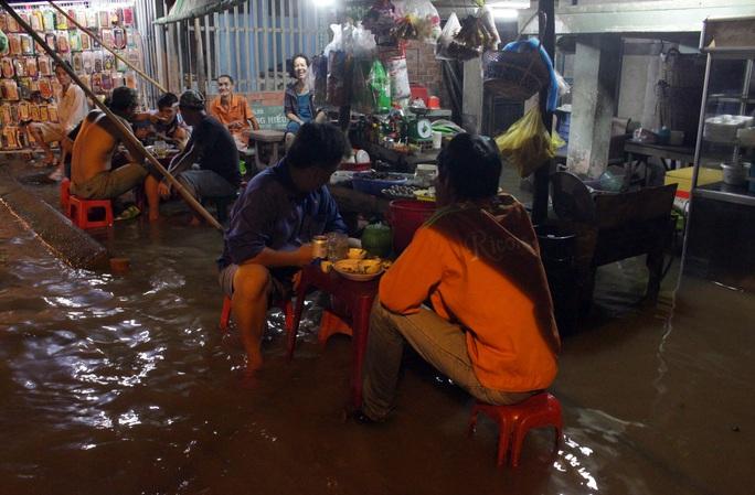 Người dân cũng thản nhiên ngồi nhậu giữa dòng nước ngập. Anh Long chia sẻ: Bây giờ đường cũng ngập quá rồi, về nhà đâu có được. Vậy là anh em vào quán làm vài chai cho vui, tiện chờ nước rút luôn.