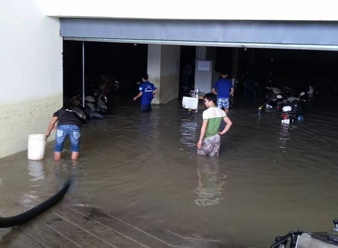 Nước bên trong hầm xe vẫn chưa thể rút và mức nước còn khá cao, gây khó khăn trong việc đi chuyển xe ra ngoài.