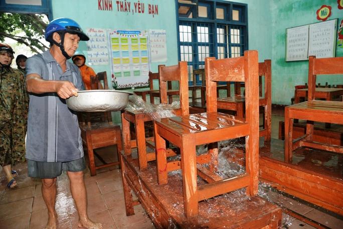 Các thầy cô giáo tranh thủ vệ sinh bàn ghế, đợi nước rút để tiếp tục dạy học trở lại. Ảnh: Tử Trực