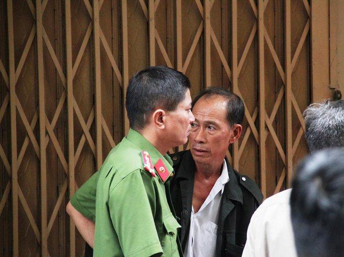 Ông Trung (áo khoác đen) như chết lặng khi biết các con và cháu mình đều đã thiệt mạng trong vụ cháy.