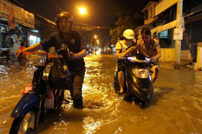 Hầu hết xe máy di chuyển qua vùng nước sâu trên đường Lê Văn Lương lúc này đều chết máy, phải dắt bộ đi tìm chỗ sửa xe.