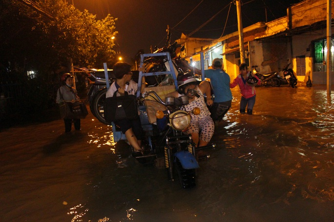 Những xe ba gác xuất hiện tại các đoạn đường ngập để giải cứu các phương tiện chết máy qua các đoạn nước ngập với giá khoảng 50.000 - 100.000 đồng.