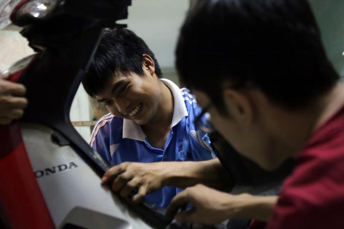 Hai chàng sinh viên Đại học Bách Khoa mượn đồ nghề để sữa chữa xe miễn phí cho các bạn sinh viên.