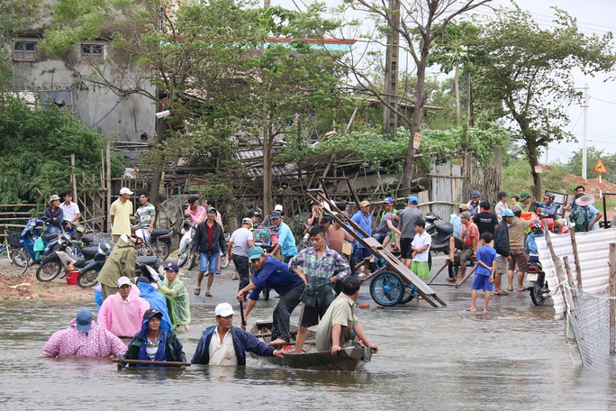 Người dân dùng ghe và xe bò đưa xe máy và người sang khỏi vùng bị ngập