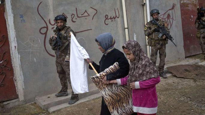Người dân mang cờ trắng trong khi quân đội Iraq tìm kiếm thánh viên IS ở ngoại ô Mosul. Ảnh: AP