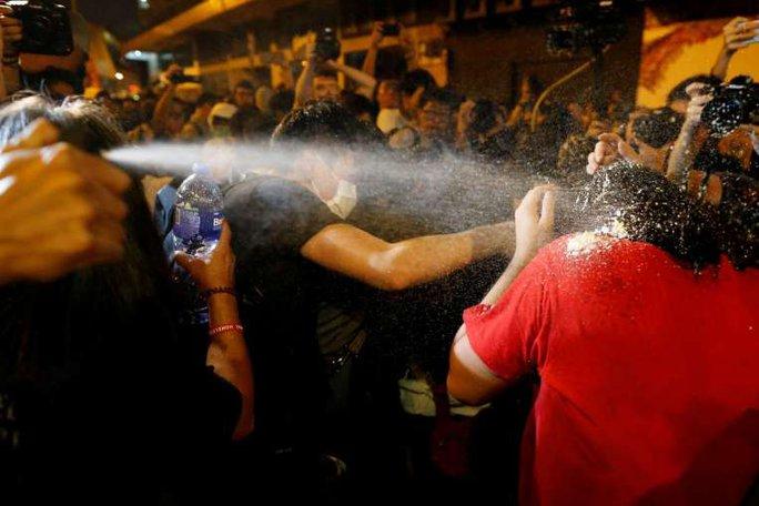 Cảnh sát bắn hơi cay vào người biểu tình. Ảnh: REUTERS