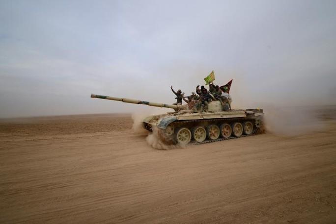 Chiến binh người Shiite lái xe tăng về phía Tal Afa, phía Tây Mosul hôm 16-11. Ảnh: REUTERS