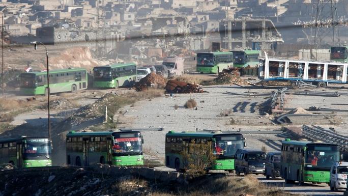 Hơn 40 xe buýt và xe cứu thương đưa người dân tới tỉnh Idlib. Ảnh: REUTERS