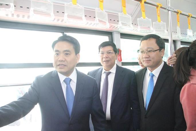 Chủ tịch UBND TP Hà Nội Nguyễn Đức Chung (bìa trái) là một trong những hành khách đầu tiên khi xe buýt nhanh chính thức vận hành ngày 31-12