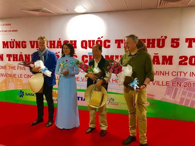 Bà Nguyễn Thị Thu, Phó Chủ tịch UBND TP HCM, tặng hoa và quà cho ông Chappe Bertrand (thứ hai từ phải sang) và 2 vị khách may mắn