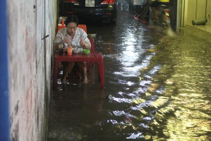 Một người đàn ông bình thản ngồi ăn hủ tiếu tại con hẻm nhỏ kế bên Bến xe Miền Đông (quận Bình Thạnh). Ngập thì ngập nhưng cứ phải no bụng cái đã! - anh vui vẻ nói