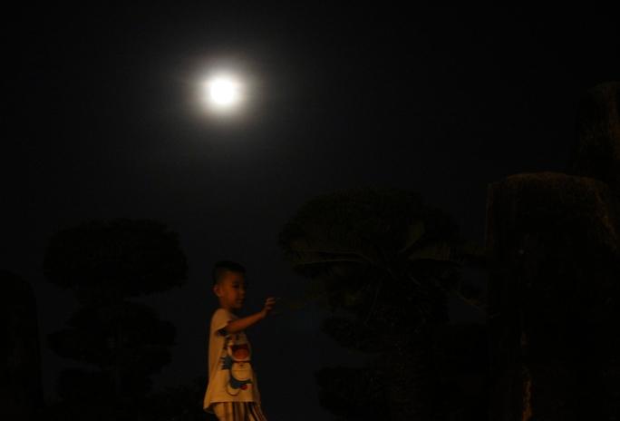 Một đưa trẻ được bố mẹ đưa ra công viên Bạch Đẳng để ngắm siêu trăng.