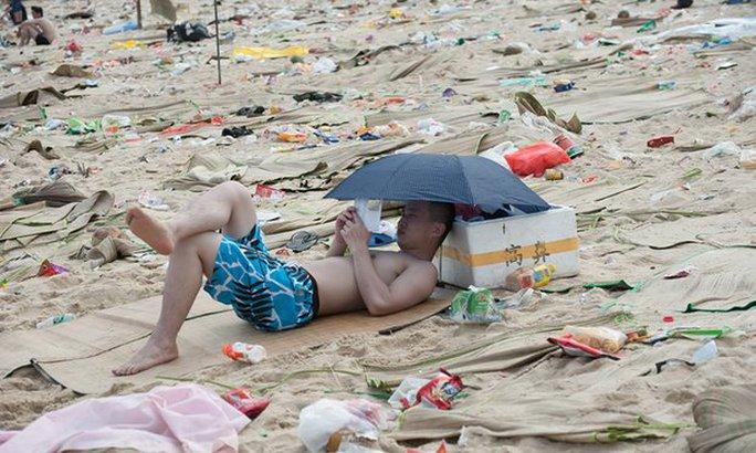 Du khách đọc sách trên bãi biển toàn rác ở Trung Quốc. Ảnh: Barcroft Media