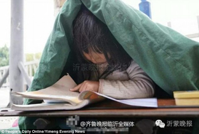 Hình ảnh cô bé 6 tuổi co ro học bài trong chăn trên phố khiến người xem xúc động. Ảnh: Peoples Daily