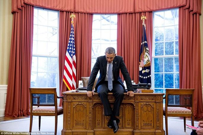 Tổng thống Obama ngồi cả lên bàn trầm tư suy nghĩ trước cuộc họp trực tuyến với các nhà lãnh đạo châu Âu vào ngày 23-12-2016.