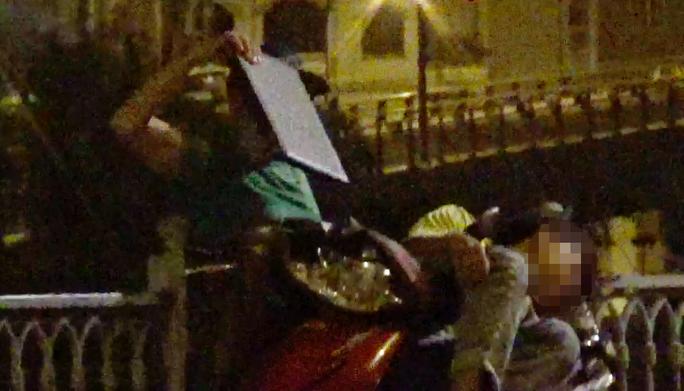 Môt đối tượng hai ngón đang lấy laptop của một thanh niên tại chân cầu Mống.